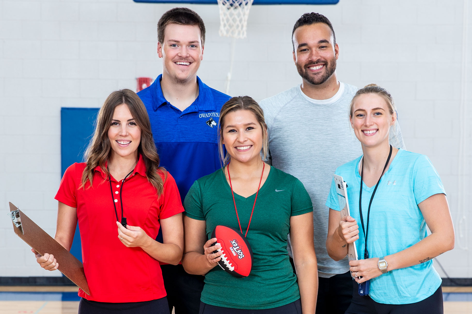Five physical education teachers smile in a gymnasium. Two men are in the back row and three women are in the front row.